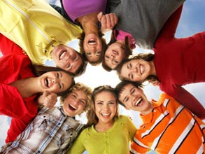A group of smiling people huddling with their heads together, shot from the ground.